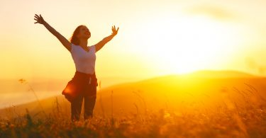 Femme heureuse avec coucher de soleil